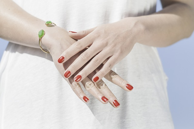 červeně nalakované nehty